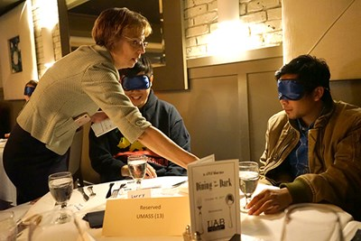 Deb Finch helps blindfolded students during the Dining in the Dark fundraiser last fall