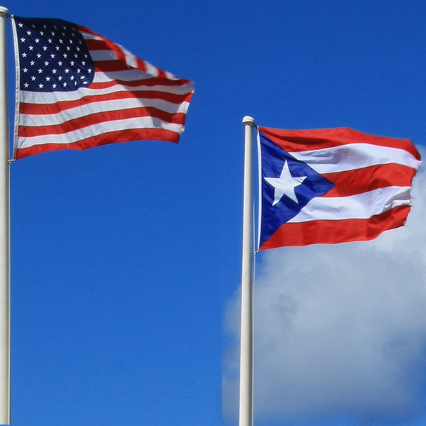 United States and Puerto Rican flags flapping in the wind.