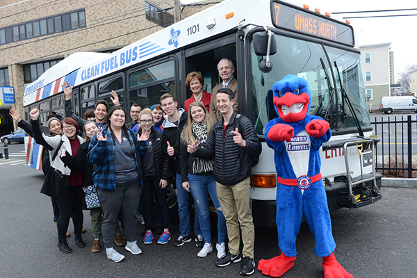 Chancellor Jacquie Moloney joins Rowdy and a dozen students at the University Crossing bus stop to celebrate the university's new collaboration with the LRTA and MVRTA.