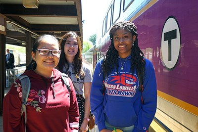 Three students stand outside a commuter rail train in Lowell