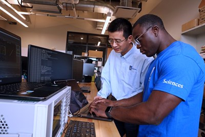 Xinwen Fu, left, and undergraduate student Chukpozohn Erastus Toe conduct cybersecurity research