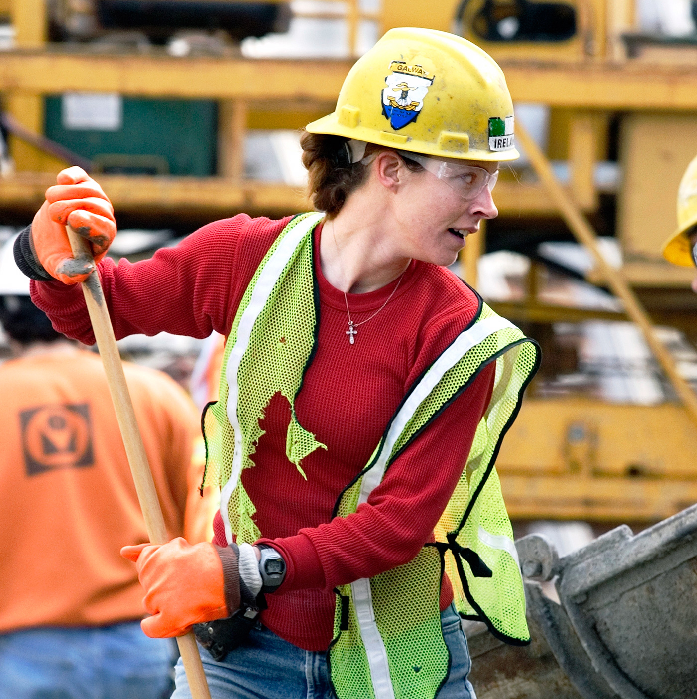 A young woman wearing safety gloves, hard hat and safety vest holds a broom. Future of Work photos by Paul Shoul woman construction