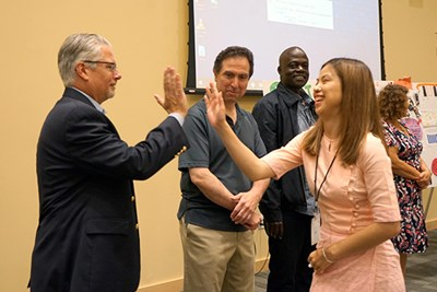 A GE2 student high fives faculty member Michael Ciuchta