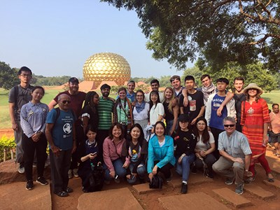 Students pose for a group photo in front of the Matrimandir