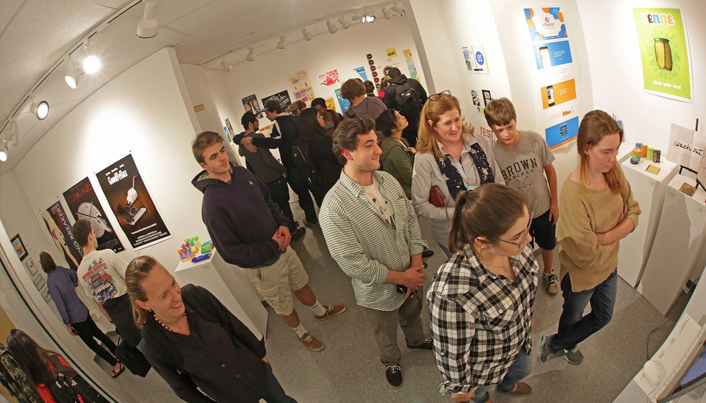A large group of students and professors looking at artwork from a gallery at UML's Graphic Design Show.