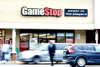 Cars and people in a parking lot in front of a GameStop store