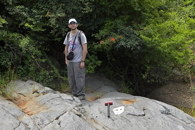 Richard Gaschnig stands on rock with hammer at feet