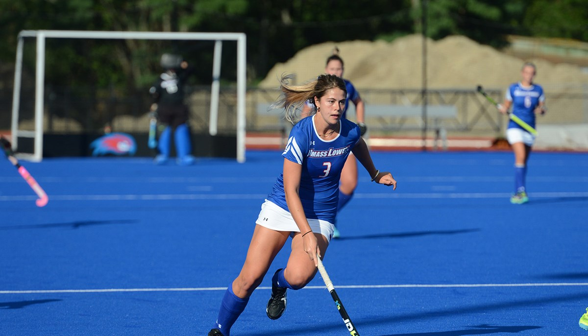 UML student Georgia Cowderoy playing field hockey on the Wicked Blue turf