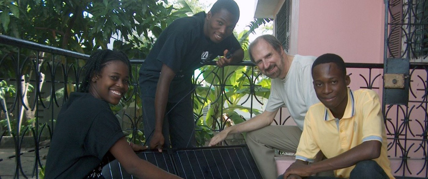 UMass Lowell Professor, Bob Giles poses with three Haitian teens while holding solar panels.