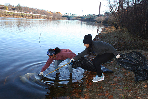 Graduate students Swati Dileep, left, and Sri Kuppa fish a piece of plastic out of the Merrimack River during Graduate Volunteer Day.