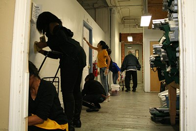 Grad students clean walls at the Lowell Transitional Living Center