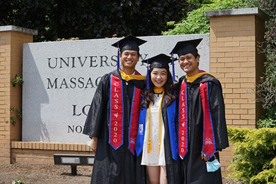Two male Asian students flank a female Asian student in the regalia in front of North Campus sign