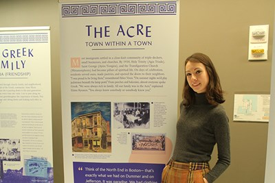 UMass Lowell honors history major Sophie Combs poses by the first panel in an exhibit on Greek immigration to Lowell