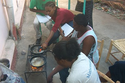 Dayana Alabre checks the temperature of pans used in a cook-off at a demonstration of eco-friendly fuel.