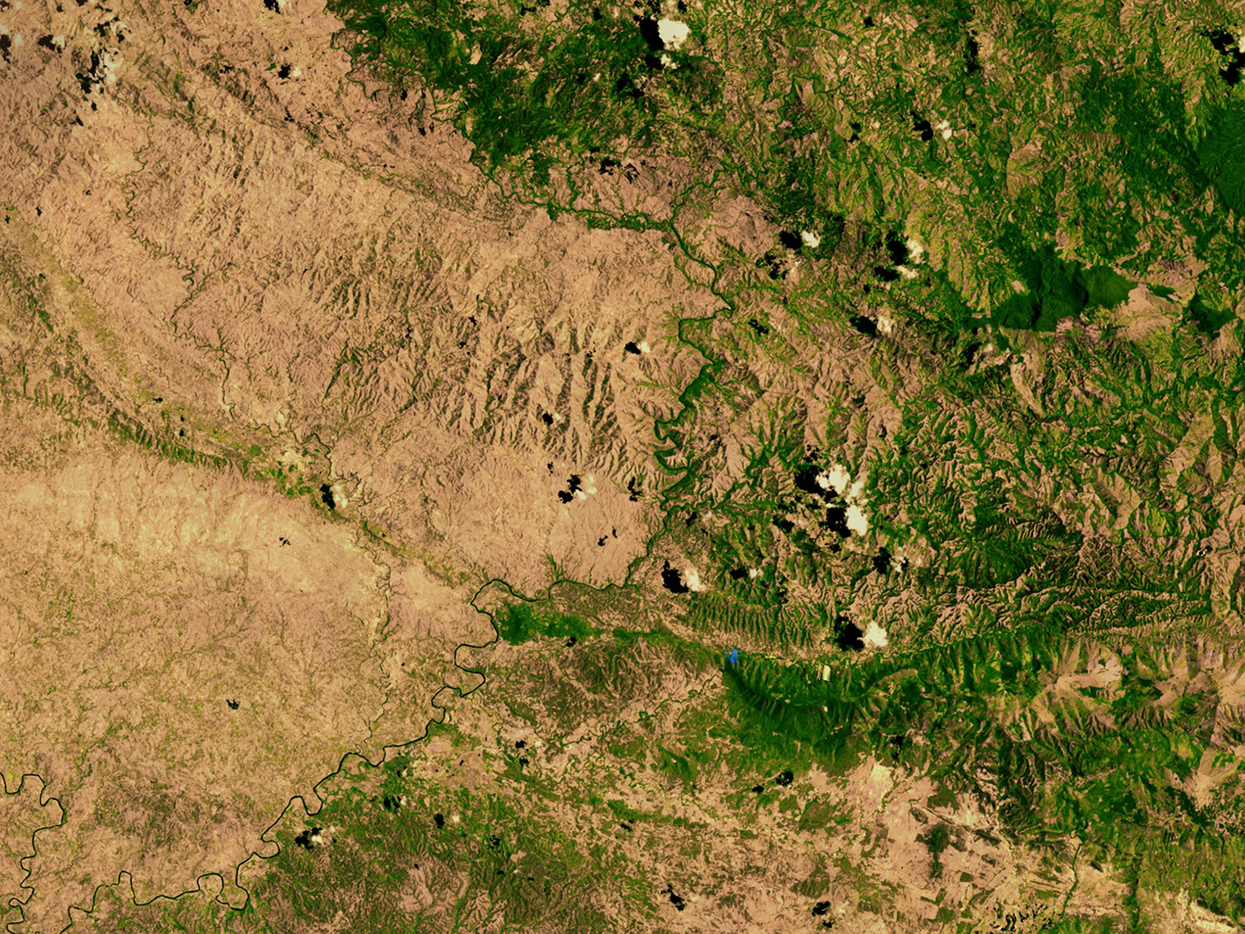 A NASA satellite image of the border between the denuded landscape of Haiti (left) and the Dominican Republic (right).