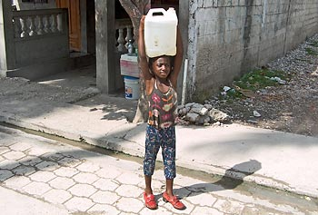 A young girl fetches contaminated water from a community well in Les Cayes, Haiti.