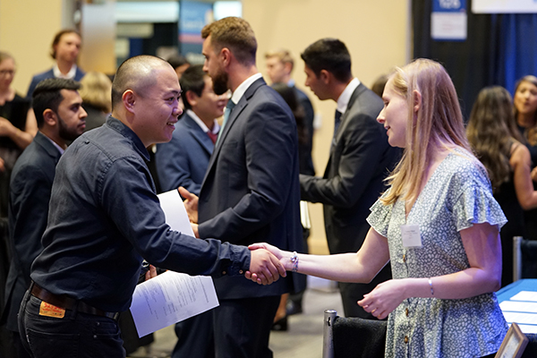 A student shakes hands with Northwestern Mutual campus recruiter Courtney Pollard during the Accounting and Finance Career Fair at University Crossing.