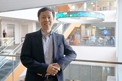 Assoc. Prof. Hieu Phan stands in front of the stock ticker at the business school