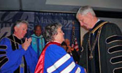 UMass President Jack Wilson adorns Barbara Hogan with her honorary doctorate as UMass Lowell Chancellor Marty Meehan applauds.