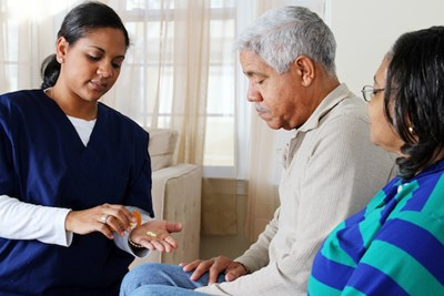 Home care worker helping elderly with medications