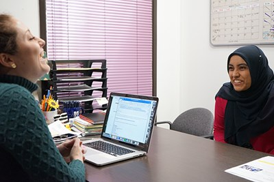 UML Honors College advisor Erin Maitland (left) shares a laugh with transfer student Rabia Haider.