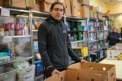 UML Honors computer science major Joseph Calles has volunteered at Central Food Ministry for more than a year