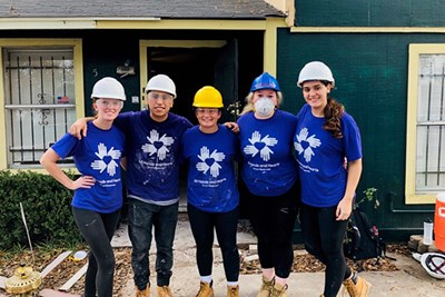 UML students stand in front of the house they helped rebuild in Houston