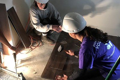 Student volunteers lay down flooring in the home