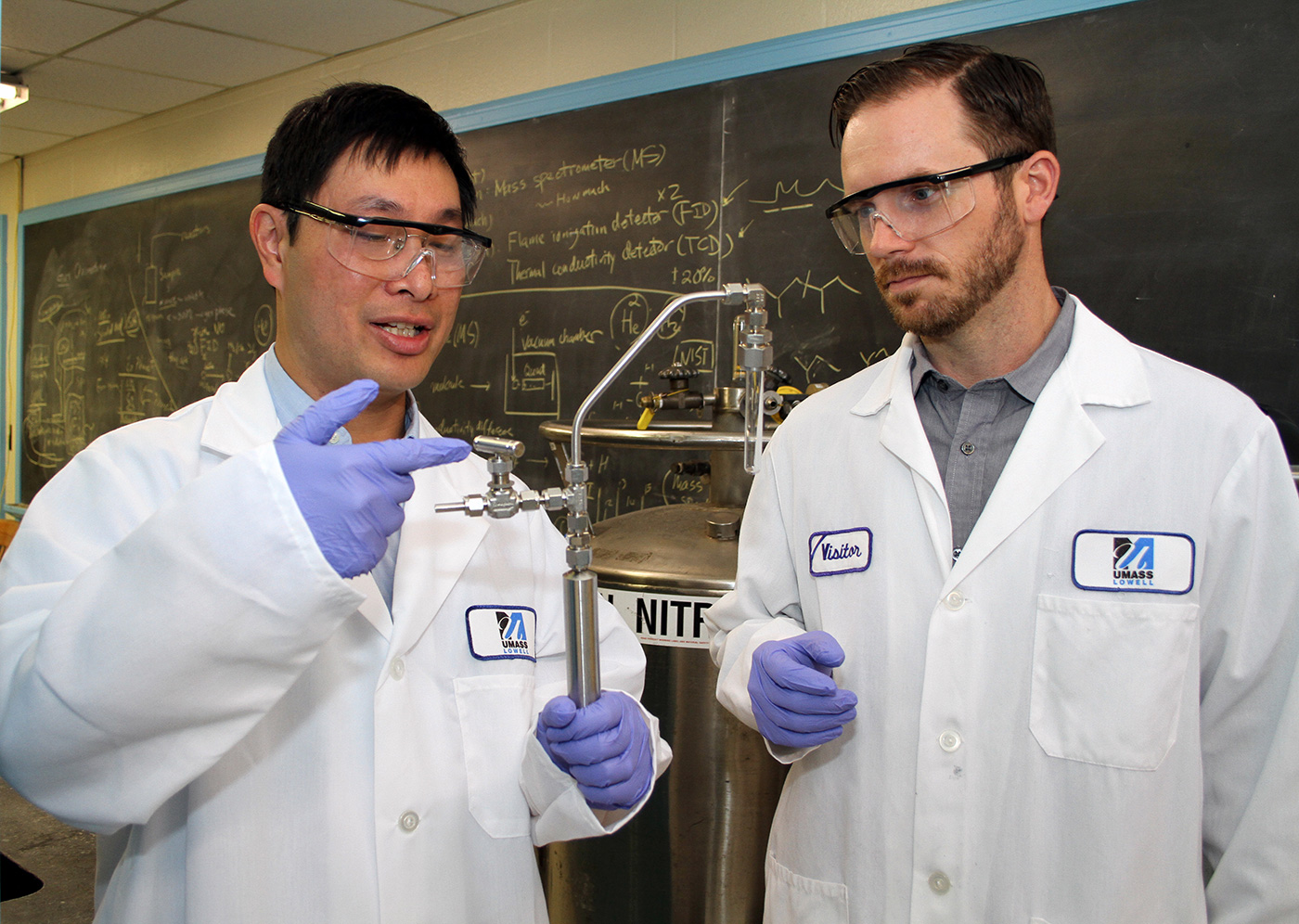 Asst. Profs. Hsi-Wu Wong and Hunter Mack examine the reactor used in creating biofuels in the lab.