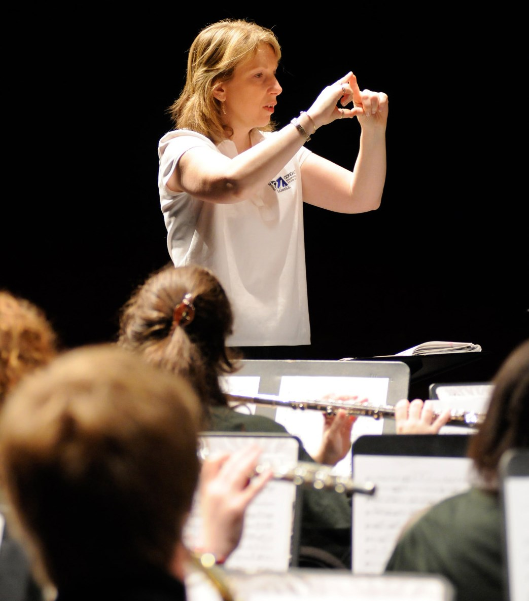Conductor Deb Huber of the University of Massachusetts Lowell explains a musical phrase to her concert band ensemble.