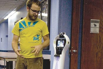 Hugo, an augmented VGo Communications' VGo telepresence robot, is shown being driven remotely by a human operator (visible on Hugo's screen). Actively participating in a mobile conversation with Hugo is Adam Norton, a UMass Lowell fine arts graduate now working as an educator and designer in Yanco's Robotics Lab.