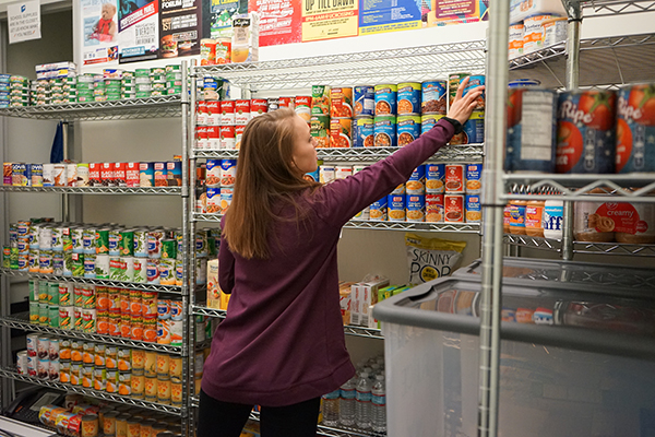 A work-study student stocks shelves at the UMass Lowell food pantry in University Crossing.