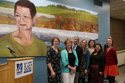 As the image of Nina Coppens gazes away, gathering to celebrate the late dean's student-created portrait are (from left) Coppens' daughter Katie, Chancellor Jacquie Moloney, Nina's husband, Paul Coppens, daughter Lindsay, student artists Julie Howard '18, Yahira Torres, '19 and Adel diPersio '19.