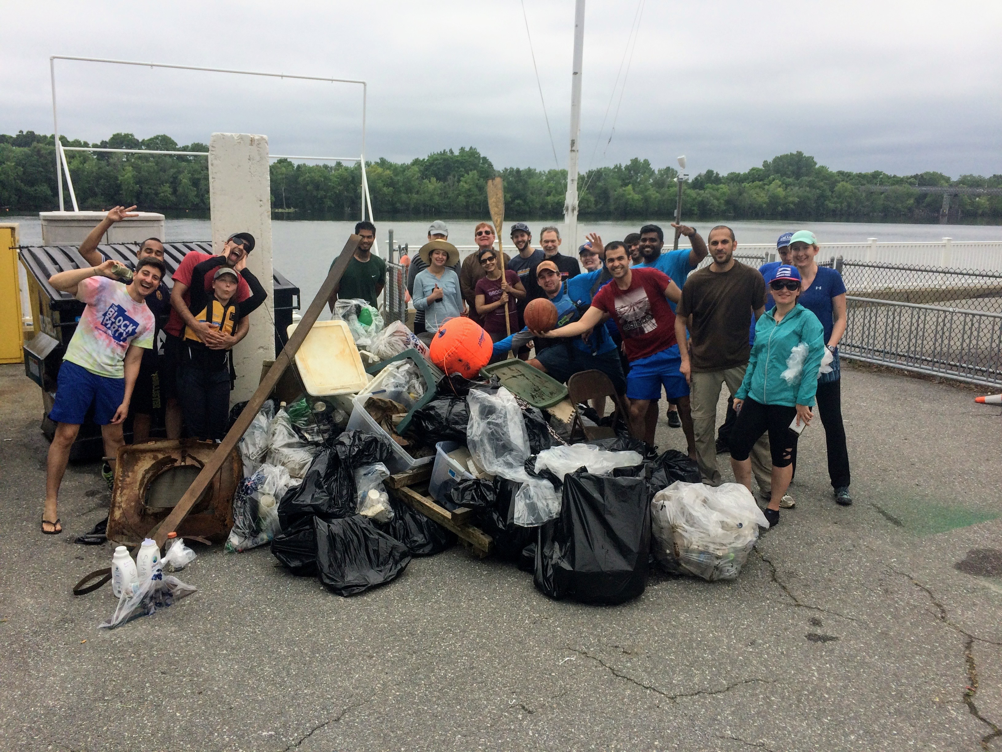 Proud group of people gathered around a large pile of debris they removed from the river bank.