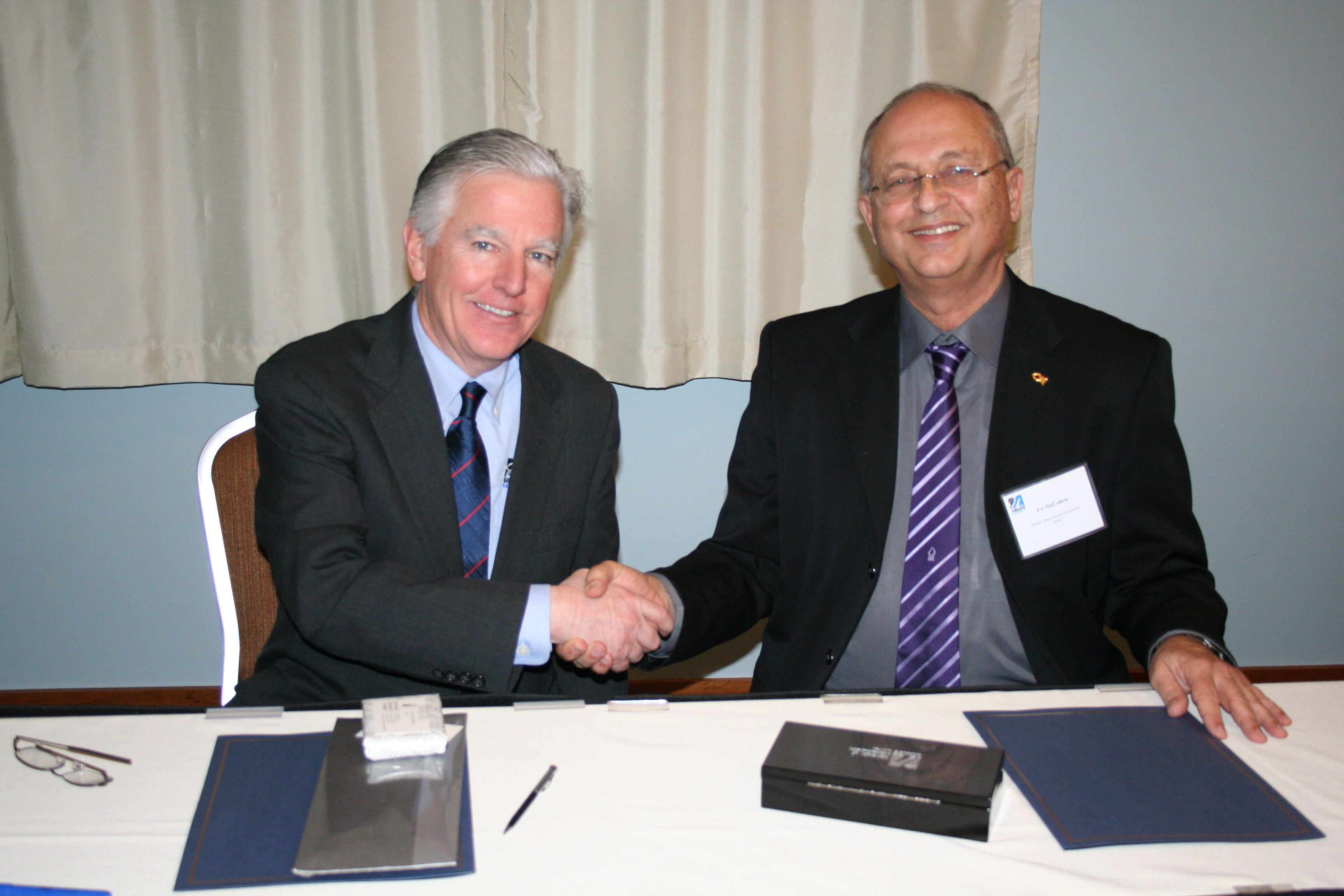 Chancellor Marty Meehan and Rector Zvi HaCohen of Israel's Ben-Gurion University sign an agreement that outlines areas of academic, research and experiential learning collaboration.