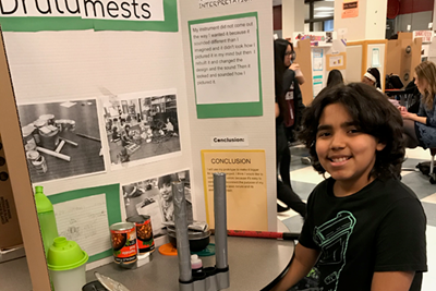 Stoklosa Middle School fifth grader Kedwin Santiago Torres proudly shows off his part in the EcoSonic Project during the recent regional science fair in Lowell.