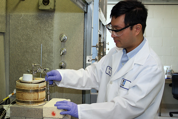 In Asst. Prof. Hsi-Wu Wong's prototype reactor setup, a sample of biomass-waste mix in a glass tube is heated without oxygen in a furnace to 500 degrees Celsius to pyrolize (break down) the mix into biofuel, which then collects in a steel cylinder.