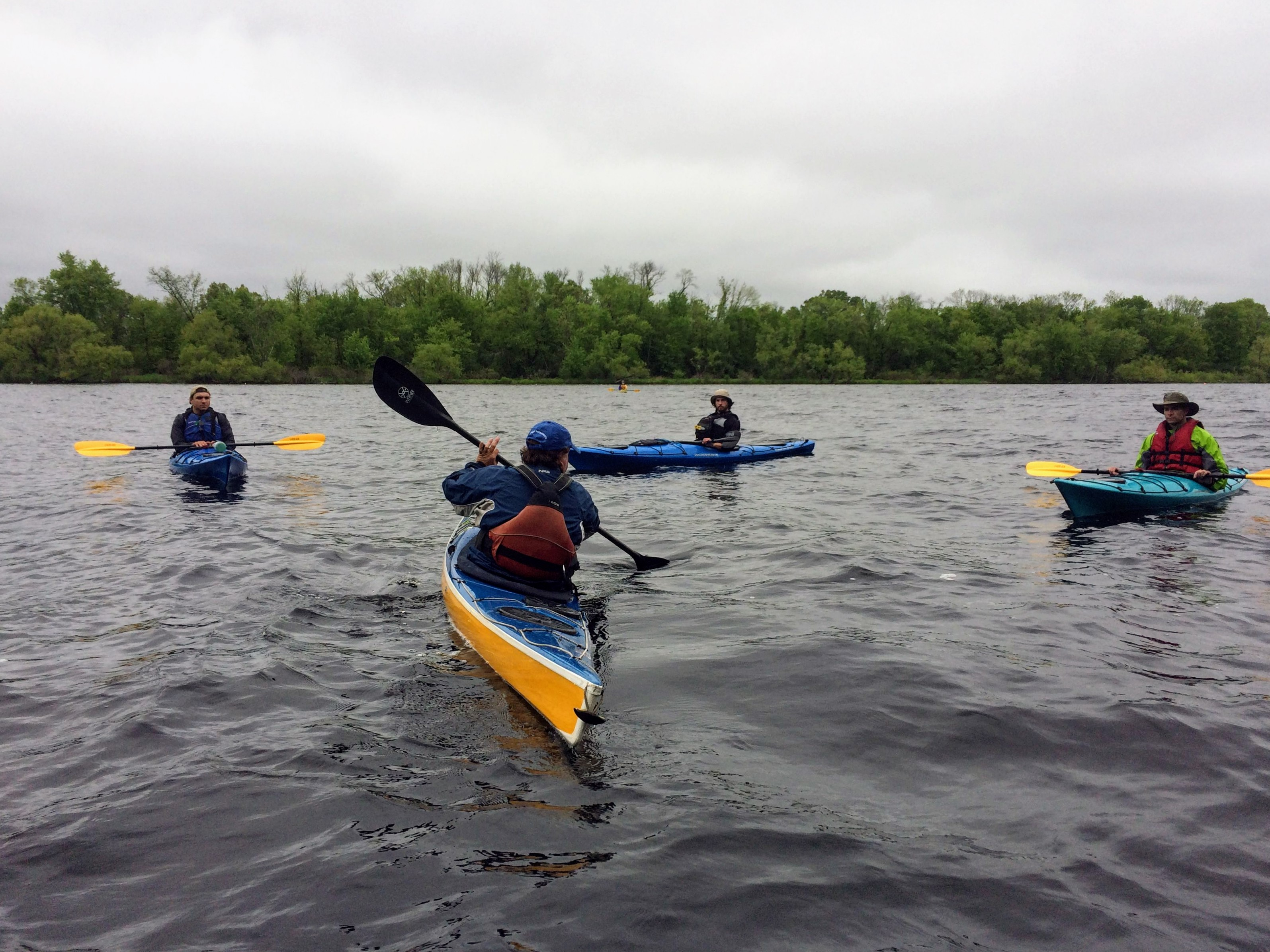 Kayak strokes class. One kayaker instructing three others.