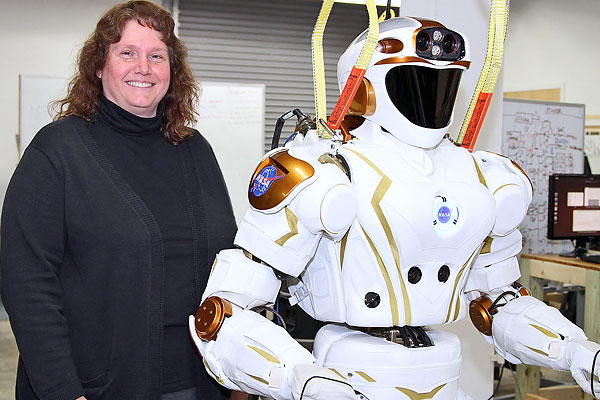 "Prof. Holly Yanco, director of the university's New England Robotics Validation and Experimentation (NERVE) Center, poses with NASA's high-tech humanoid robot named ""Valkyrie."""