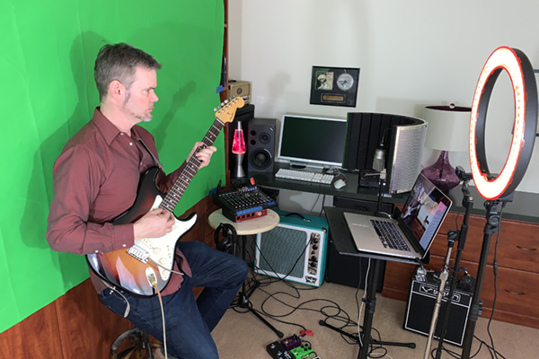The music faculty faces unique challenges in moving classes and rehearsals online. Prof. John Shirley has organized a virtual teaching station in his home. During class, he flashes familiar campus scenes on the green screen behind him.