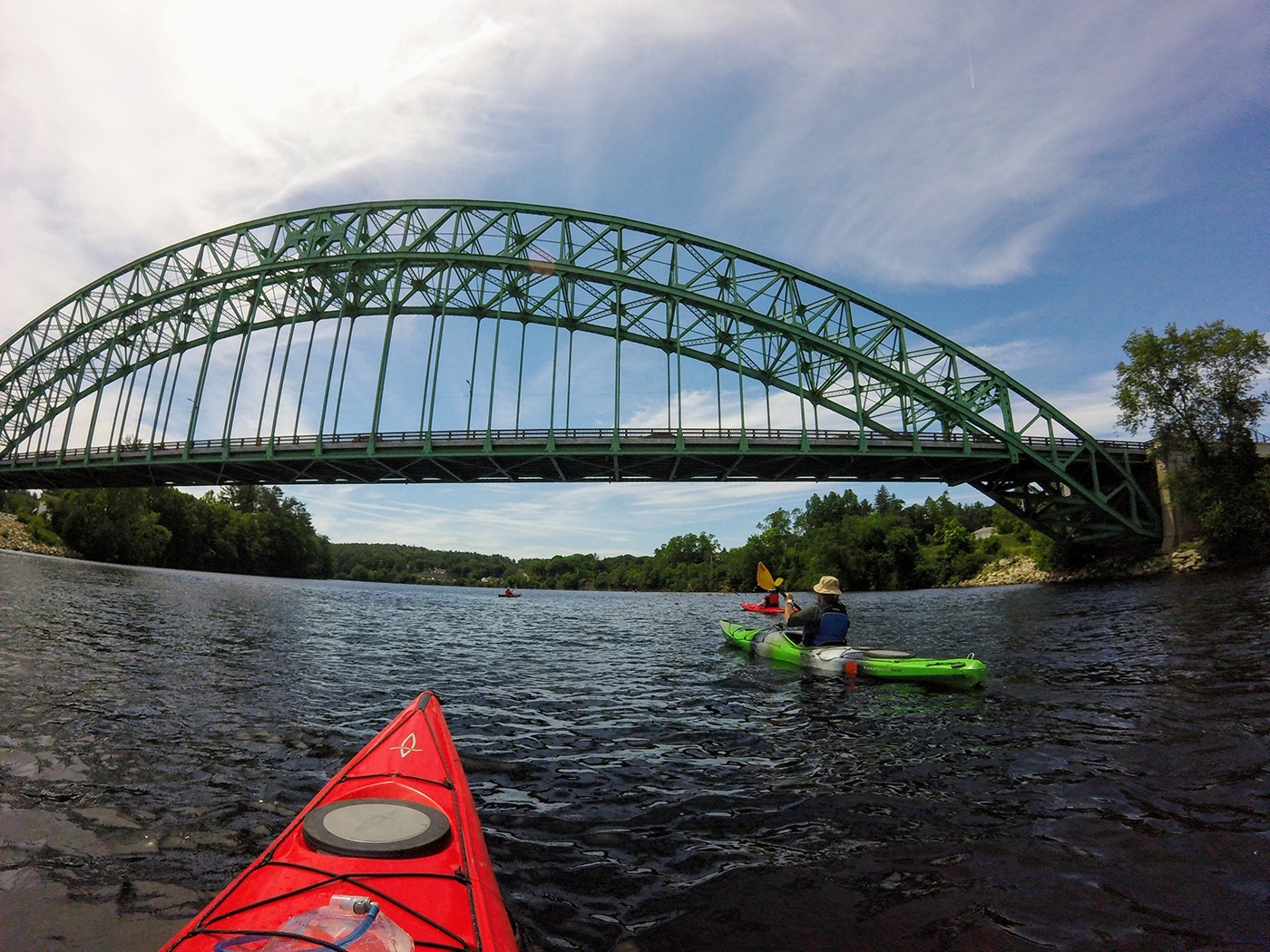 Kayakers approaching under a large green arch bridge.