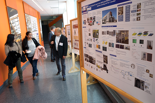 IoT Forum guests walk past posters of MassTech Collaborative-funded projects after breakout sessions at the Pulichino Tong Business Center.