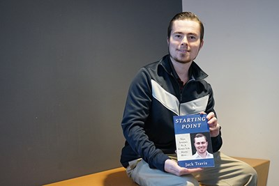 Jack Travis poses with his new book in Pulichino Tong Business Center