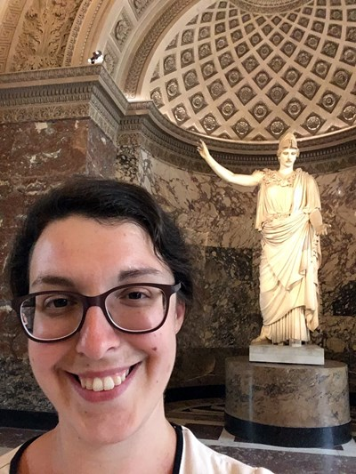 UMass Lowell Assistant Professor of History Jane Sancinito  poses for a picture in front of  the statue of Athena at the Louvre museum.