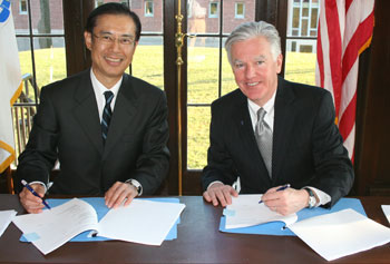 Toyoaki Miwa, president of executive education firm Abitus, signs an agreement with Chancellor Marty Meehan for UMass Lowell to offer its MBA program in Japan.