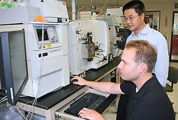 Asst. Prof. Jin Xu and postdoctoral researcher Tyler Carter at the Massachusetts BioManufacturing Center at UMass Lowell.