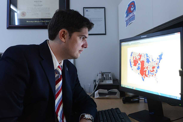 Assoc. Prof. Joshua Dyck, director of the Center for Public Opinion, looks at an electoral map of the U.S.