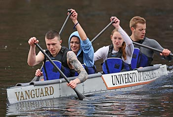 "UMass Lowell team members race their self-designed and built concrete canoe, dubbed 'Vanguard,""'on Bare Hill Pond in Harvard on April 27."