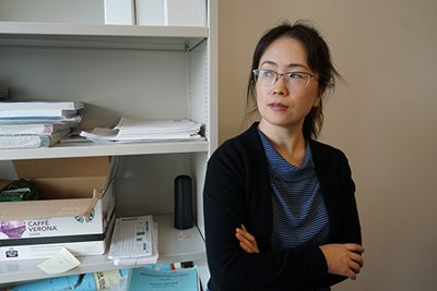 Business professor Julie Zhang looks out her office window