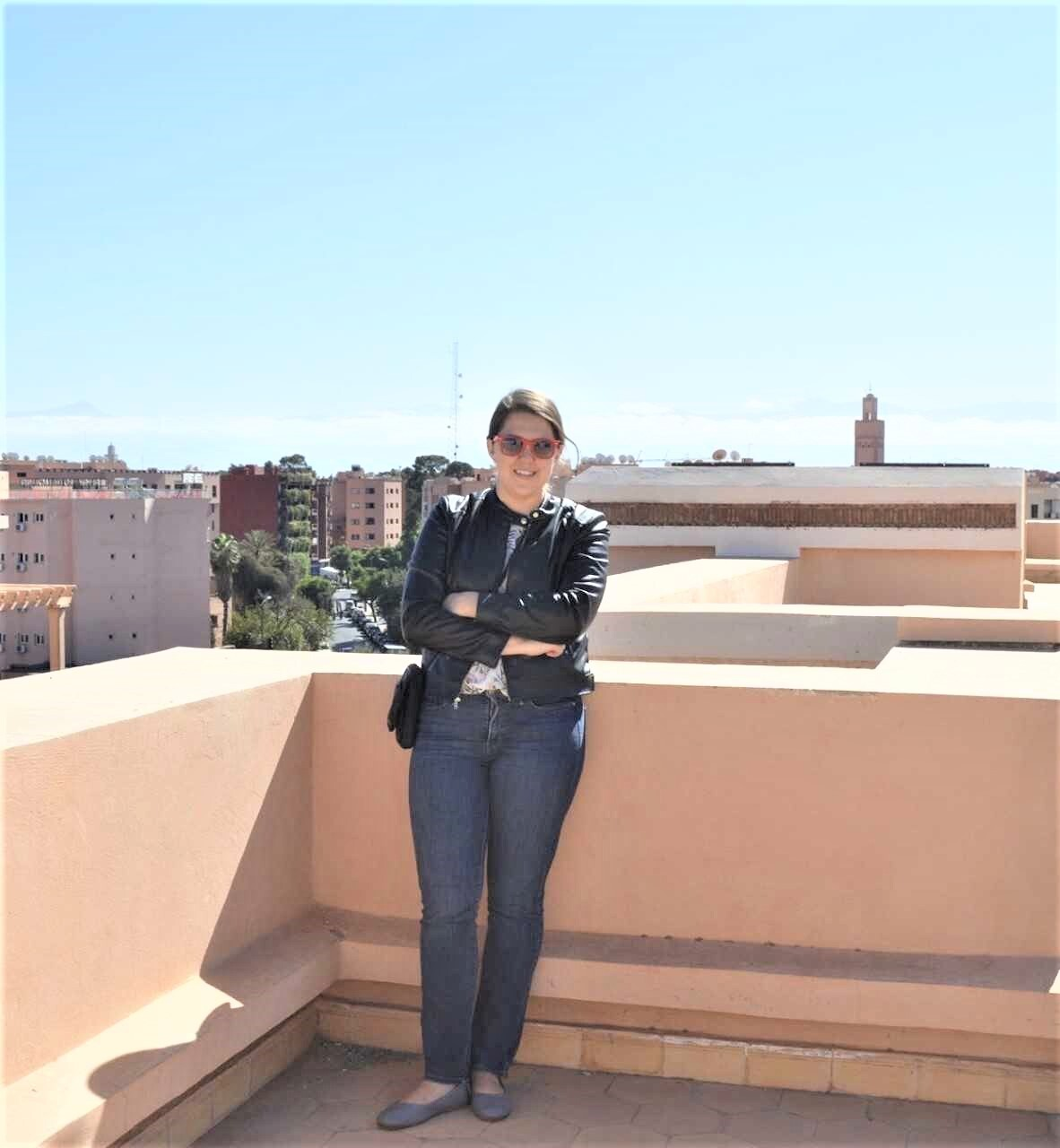UMass Lowell History Department Alumna Kate DiTullio poses on a rooftop with the Marrakech skyline behind her.